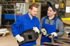 Instructor teaching trainee how to weld metal Royalty Free Stock Photo