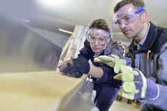 Instructor and trainee doing carpentry. Instructor showing trainee how to use sawing machine Royalty Free Stock Photo