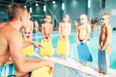 Instructor training children in the pool. Boys with swimming goggles ready for swimming and stands near water. Healthy activity in pool. Sportive kids activity Royalty Free Stock Photo