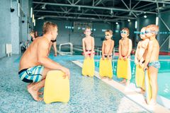 Instructor training children in the pool. Boys with swimming goggles ready for swimming and stands near water. Healthy activity in pool. Sportive kids activity Stock Images
