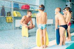 Boys with swimming goggles and planks. Instructor training children in the pool, view from back. Boys with swimming goggles and planks for swimming stands near Stock Images