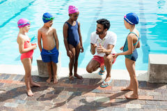 Instructor training children at poolside. Male instructor training children at poolside Royalty Free Stock Image