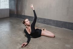Instructor woman doing stretching. Studio shot, gray wall royalty free stock images