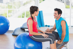 Instructor and woman with exercise ball at a bright gym Stock Photo