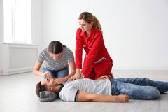 Instructor with woman practicing first aid on unconscious man. Instructor with women practicing first aid on unconscious men indoors royalty free stock image