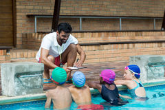 Instructor writing on clipboard while explaining little swimmers at poolside Stock Image