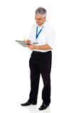 Instructor writing clipboard. Senior driving instructor writing on clipboard isolated on white background stock image
