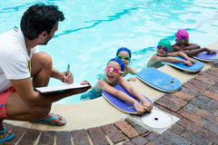 Instructor writing on clipboard with swimmers at poolside. Male instructor writing on clipboard with little swimmers at poolside Royalty Free Stock Photography