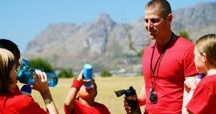 Instructor y agua potable de los niños en el campo de bota metrajes