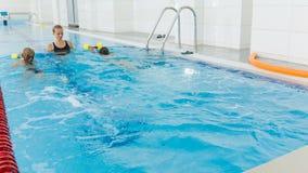Instructor y niño que hacen ejercicios en piscina El coche enseña a muchachas a nadar almacen de metraje de vídeo