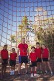 Instructor y niños que se unen en el campo de bota Fotografía de archivo
