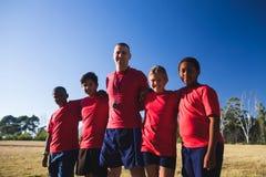 Instructor y niños que se unen en el campo de bota Imagen de archivo libre de regalías