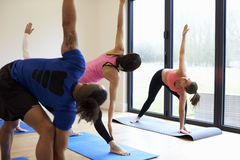 Instructor With Yoga Class At Gym Stock Image