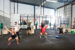 Instructores que ayudan a atletas en el ejercicio con foto de archivo