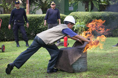 Instructors Firefighters. A trainer was doing to extinguish the fire in a drum by using wet sacks at Bogor, West Java, Indonesia Royalty Free Stock Photo