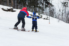 Instructors teach a child skiing. Female instructors teach a child skiing on winter resort Royalty Free Stock Images