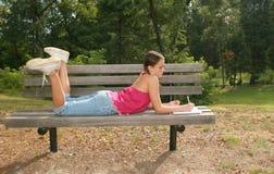 Instruisez l'écriture de fille dans le cahier sur un banc Images stock