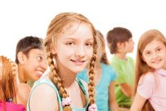 Instruisez la fille avec des queues de cheval et le groupe d'amis Image stock