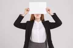 Instruisez la fille tenant le livre blanc à côté de son visage Fille jugeant un carton vide prêt pour le texte Photographie stock