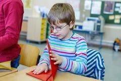 Instruisez le garçon d'enfant avec des verres jouant avec le papier coloré et faisant les chiffres géométriques Photo stock