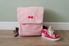 Instruisez le sac à dos et les espadrilles sur le plancher dans un intérieur de maison Photographie stock libre de droits