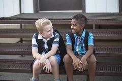 Instruisez les étudiants parlant ensemble tout en se reposant sur les escaliers à l'école photographie stock