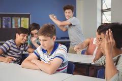 Instruisez les amis intimidant un garçon triste dans la salle de classe Photographie stock libre de droits