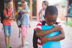 Instruisez les amis intimidant un garçon triste dans le couloir Photos stock