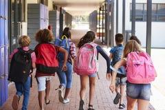 Instruisez les enfants courant dans le couloir d'école primaire, vue arrière photos libres de droits