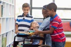 Instruisez les enfants donnant des livres à la fille handicapée dans la bibliothèque Photo stock
