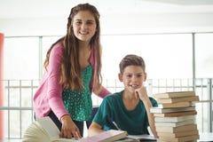 Instruisez les enfants faisant des devoirs dans la bibliothèque à l'école Photos libres de droits