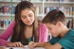 Instruisez les enfants faisant des devoirs dans la bibliothèque à l'école Image libre de droits