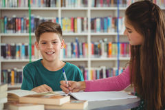 Instruisez les enfants faisant des devoirs dans la bibliothèque à l'école Photographie stock libre de droits
