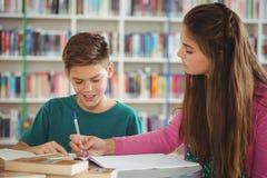 Instruisez les enfants faisant des devoirs dans la bibliothèque à l'école Images stock