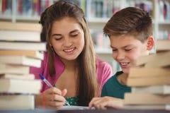 Instruisez les enfants faisant des devoirs dans la bibliothèque à l'école Photo stock