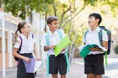 Instruisez les enfants parlant entre eux tandis que des livres de lecture dans le campus Photo stock