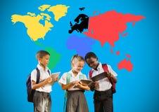 Instruisez les enfants regardant des comprimés devant la carte colorée du monde Photo stock