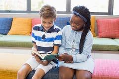 Instruisez les enfants s'asseyant ensemble sur le sofa et le livre de lecture Photos stock