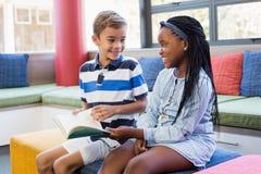 Instruisez les enfants s'asseyant ensemble sur le sofa et lisant un livre Images libres de droits