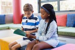 Instruisez les enfants s'asseyant ensemble sur le sofa et lisant un livre Photo stock