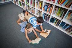 Instruisez les enfants se trouvant sur le plancher et lisant un livre dans la bibliothèque Image libre de droits
