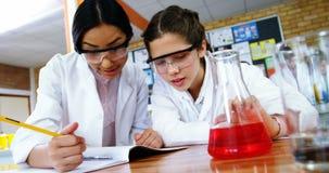Instruisez les filles écrivant dans le livre de journal tout en expérimentant dans le laboratoire à l'école clips vidéos