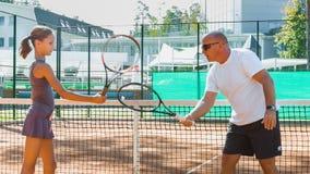 Instruktör- eller lagledareundervisningbarn hur man spelar tennis på en domstol inomhus arkivfilmer