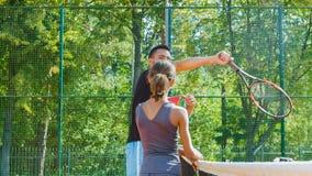 Instruktör- eller lagledareundervisningbarn hur man spelar tennis på en domstol inomhus stock video