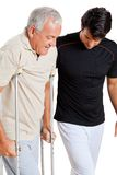 Instruktör Helping Senior Man med kryckor Arkivbild
