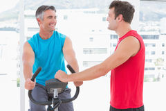 Instruktör med mannen på motionscykelen Arkivbild