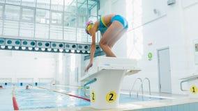 Instruktör och barn som gör övningar i simbassäng Lagledaren undervisar flickan att simma eller dyka arkivfilmer