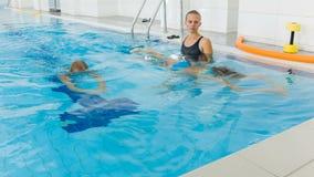 Instruktör och barn som gör övningar i simbassäng Lagledaren undervisar flickor att simma stock video