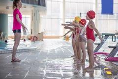 Instruktör och grupp av barn som gör övningar nära en simbassäng Royaltyfri Foto