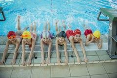Instruktör och grupp av barn som gör övningar nära en simbassäng royaltyfri fotografi